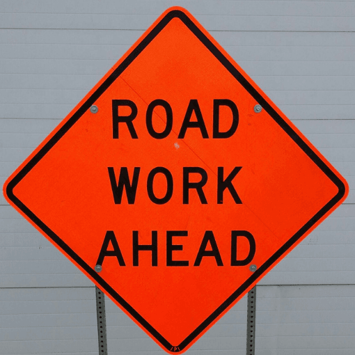 Orange construction sign reads Road Work Ahead