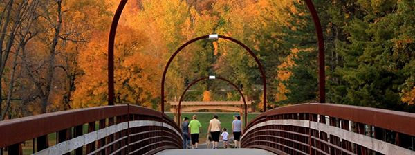 Group of people walking through a bridge in autumn